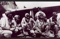 Airmen crouching under plane