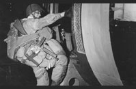 D-Day Paratrooper - A heavily burdened paratrooper, armed with a Thompson M1 submachine gun, climbs into a transport plane bound for France.
