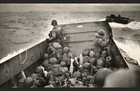 LCVP Utah - Tightly packed troops crouch inside their LCVP as it plows through a wave. In the distance is the coast of Normandy.