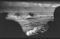 Omaha Beach - LCVPs (Landing Craft Vehicle, Personnel), or Higgins boats, head for Omaha Beach. Landing began at 6:30 am Men can be seen wading ashore; their initial objective, the bluffs above the beach. Image courtesy of National Archives, 26-G-2337