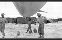Barrage Ballons - African American soldiers of the 320th Anti-Aircraft Barrage Balloon Battalion, 1st US Army prepare to deploy a barrage balloon on Utah Beach during the Normandy invasion. US forces were racially segregated until after World War II, and the 320th was one of several African American units that landed on D-Day. The barrage balloon could be moored to the ground or to a ship by a heavy mooring cable. The combination of the heavy cable and the balloon was a simple yet effective means of preventing enemy aircraft from conducting strafing or dive-bombing attacks. Image courtesy of National Archives, 111-SC-191713